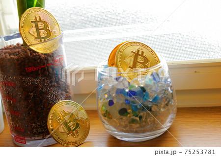 黄金色に輝く複数の仮想通貨のメダルとビットコインと植物 75253781