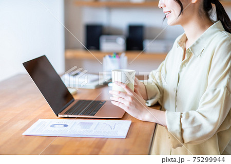 テレワークでコーヒーを飲む若い女性 75299944