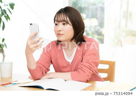 スマホでオンライン授業を受ける若い女性 75314094