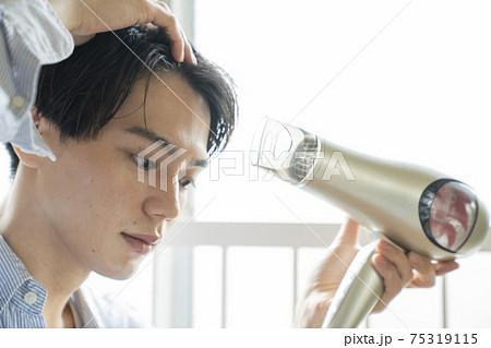 ドライヤーで髪の毛を乾かす男性 75319115