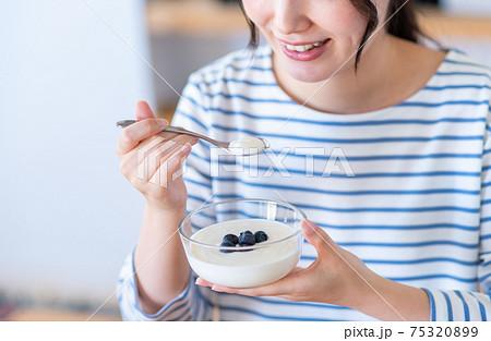ヨーグルトを食べる若い女性 75320899