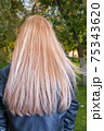 Back view of the young lady with beautiful blond straight long hairs in park 75343620