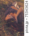 A nice lady with dark hair lies in the woods on the ground. A girl in a retro dress lies on the dried grass in the woods. 75343624
