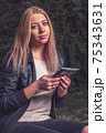 Blond haired lady doing e-learning in the park via her tablet PC. Vintage looking matte style. 75343631