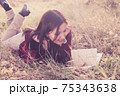 Girl lying on grass in sunset light with a book. Spring or summer warm weather relax. 75343638