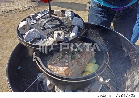野外で焼け具合を確認するダッチオーブンのローストポーク 75347705