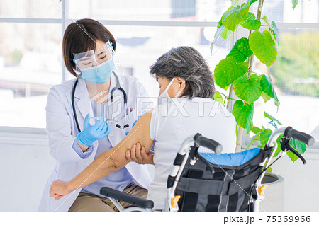 シニアにワクチンを刺す医者 75369966