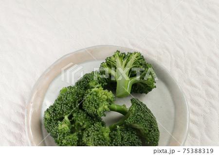 お皿に盛りつけた茹でたブロッコリー 75388319