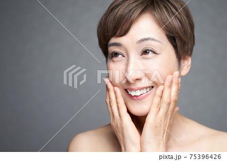 笑顔で頬に両手を当てる中年の日本人女性 75396426