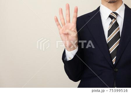 4本の指を立てるスーツを着た男性 75399516