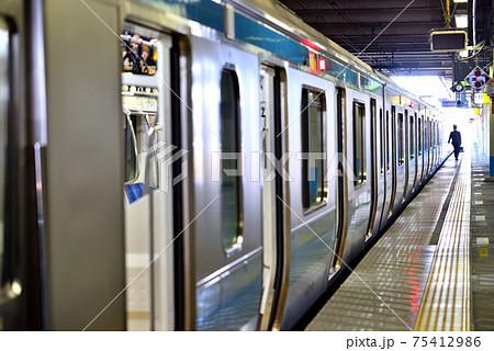 折り返し運転時間待ちのJR京浜東北線と車掌のシルエット 75412986