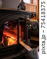 薪ストーブ(暖炉)に薪をくべる写真 75418375