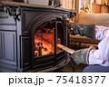 薪ストーブ(暖炉)に薪をくべる写真 75418377