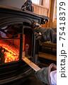 薪ストーブ(暖炉)に薪をくべる写真 75418379