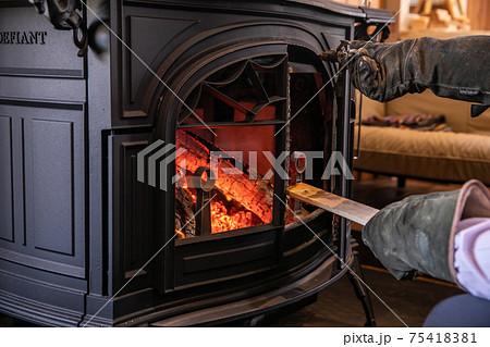 薪ストーブ(暖炉)に薪をくべる写真 75418381