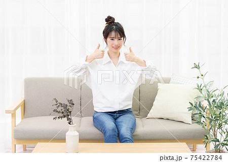 窓際のソファに座って、いいねのジェスチャーをする若い女性 75422784