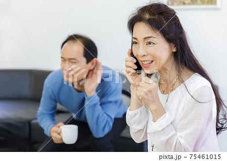 電話をする女性と聞き耳を立てる男性 75461015