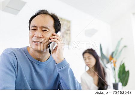 電話で通話をしている男性と会話が気になる女性 75462648