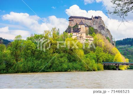 oravsky podzamok, slovakia - MAY 01, 2019: oravsky castle on the hill near the river. popular travel destination. beautiful springtime scenery in dappled light 75466525