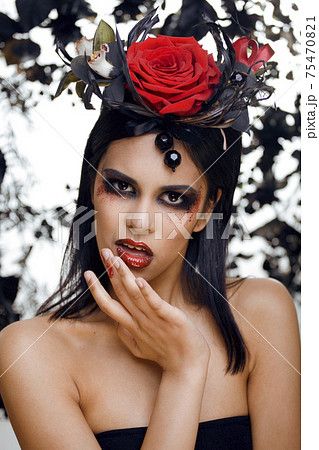 pretty brunette woman with rose jewelry, black and red, bright make up kike a vampire closeup red lips 75470821