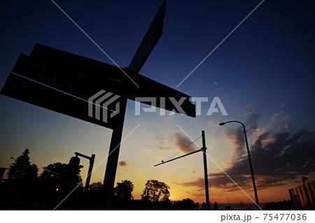 夜明けの空と案内標識のシルエット 75477036