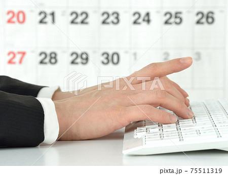 カレンダーの前でパソコン作業を行うビジネスマンの手 75511319