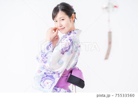 浴衣を纏い風鈴の音色を聞く女性 75533560