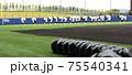 並んでいるヘルメットの後方でウォーミングアップをしている選手たち(野球場) 75540341