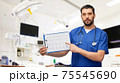 male doctor with cardiogram on clipboard 75545690