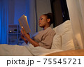 young woman reading book in bed at home 75545721