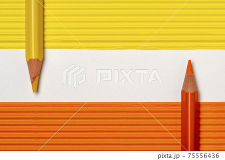 Yellow and orange pencils on colored paper sheets 75556436