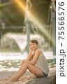 光の中に笑顔で座るハーフの女の子 75566576