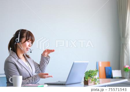 クリアマスクでオンラインミーティング_こんな高さでとジェスチャーで示す女性 75571543