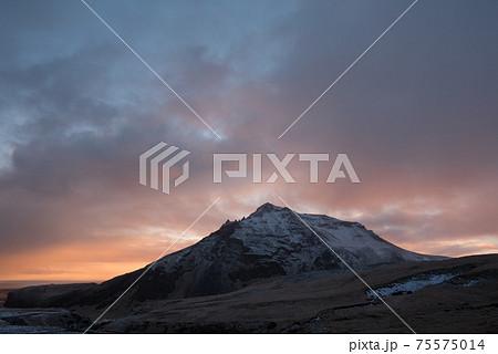 北欧アイスランドの冬期のスコゥガフォスの滝から観える夕焼けと雪山 75575014