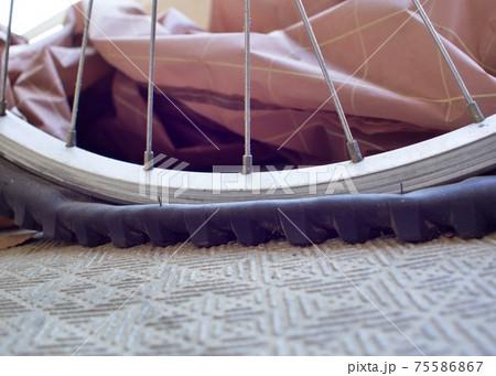 パンクして潰れているマウンテンバイクのタイヤを側面から撮影 75586867