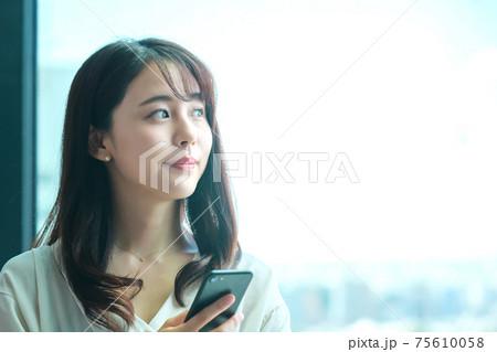 オフィスでスマホを操作する若い女性(カジュアル)  75610058