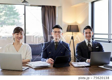 カメラ目線で笑顔のアジア人とラテン人のビジネスパーソン 75620138