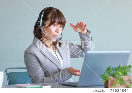 クリアマスクでオンラインミーティング_こんな高さでと身振りで説明する女性 75624844