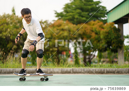 Surfers Asian man having fun with surfboards or surf skate around city streets background on a summer day. Free relax lifestyle and millennial trend concept 75639869