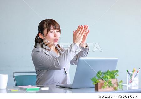クリアマスクでオンラインミーティング_上に持ち上げてと説明する女性 75663057