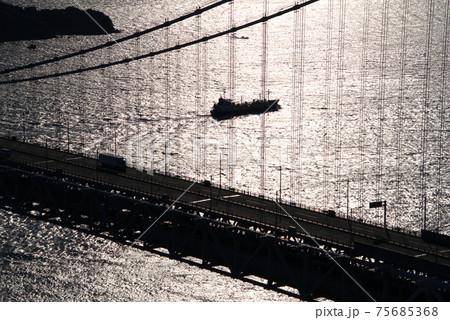 逆光で輝く瀬戸内海を行くタンカーと下津井瀬戸大橋 岡山県倉敷市 75685368