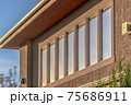 Close up of upper storey of home with rectangular windows lining the wall 75686911
