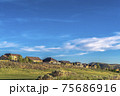 Scenic landscape of houses on a hill under vibrant blue sky on a sunny day 75686916