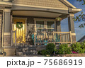 Home facade with yellow door and front porch decorated with flowers and plants 75686919