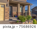 Home with landscaped yard and front porch against hill and sky background 75686926