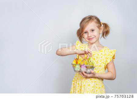 Portrait of little smiling girl with a shopping basket filled with Easter things 75703128