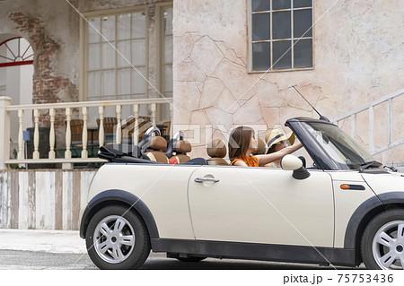 オープンカーで女子旅に出発する明るく元気な女性二人 75753436