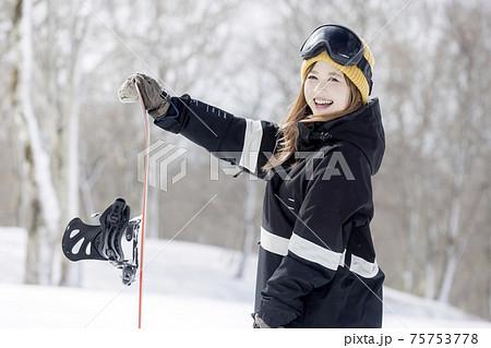 スノボを持って立つ若い女性 スノーボードイメージ  75753778