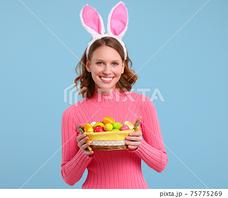 Positive young woman with bunny ears smiling and holding Easter basket in hands 75775269