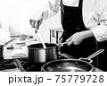 Chef cooking in a kitchen, chef at work, Black and White. 75779728